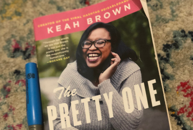 a closeup of a blue pen and a book. The book is Keah Brown's The Pretty one, featuring a young woman smiling