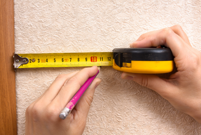 a woman's hands are using a tape measure to mark off a distance on the wall with a pencil