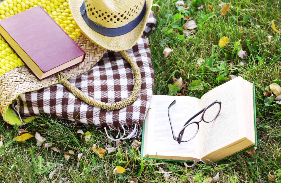 yellow straw beach bag with eyeglasses, books, a picnic blanket and a hat, spread out on a green lawn