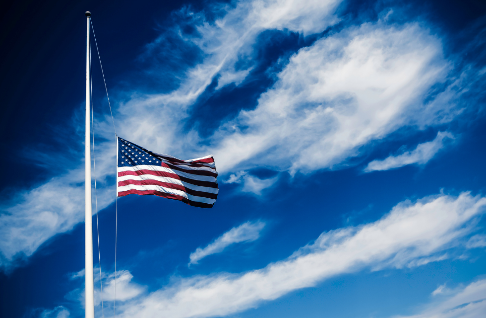 an american flag at half mast with a blue sky and clouds in background